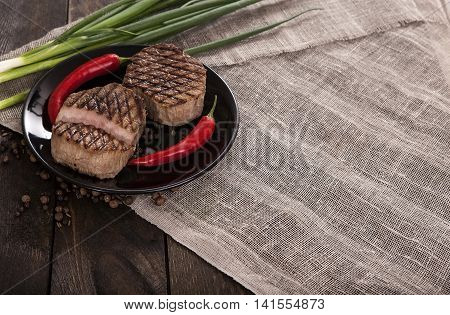 Roast beef with onions and peppers on a dark wooden table. Veal roast with vegetables