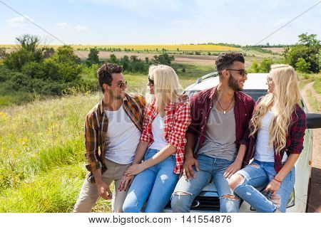 Friends sitting on car outdoor countryside people smile summer day trip