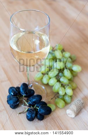 Branch of healthy red and green grape fruits and a glass of white wine on a wooden board.