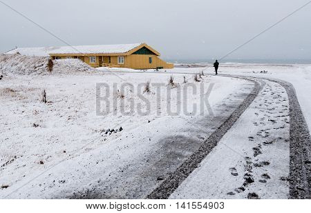 Unrecognized man walking on a snowy road to the yellow winter cottage house in Iceland