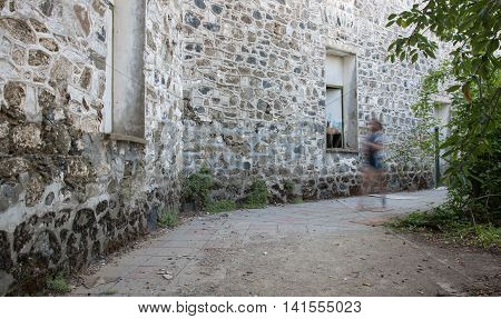 Profile of a young adult walking fast outside an abandoned and deserted building