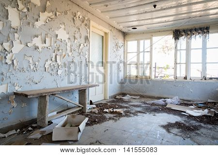 Interior of a damaged abandoned room with broken open windows and dirt on the floor