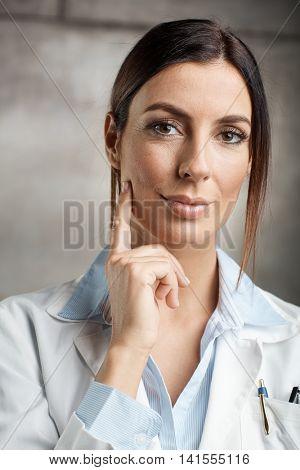 Closeup portrait of attractive female doctor in lab coat.