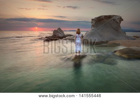 Woman standing on an unusual place - isolated stone from the shore and watching the sunrise by rocks with strange shape. Aegean Sea Greece.