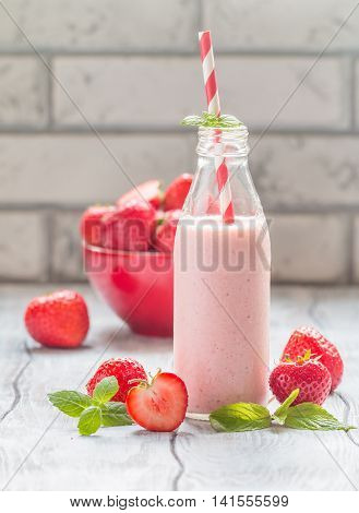 Strawberry smoothie or milkshake in a glass bottle on white rustic background, healthy food for breakfast and snack