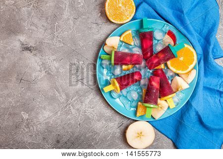Sangria popsicles with fruits and ice on gray background, top view