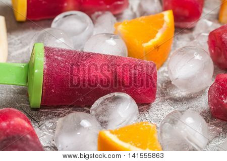 Sangria popsicles with fruits and ice on gray background