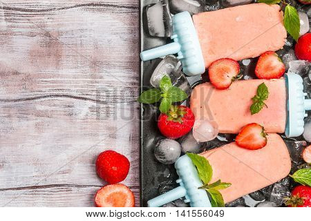 Homemade strawberry ice cream or popsicles on dark wooden table, frozen fruit juice, vegetarian food, top view