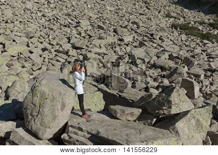 Lone woman hiker in white shirt photographing with your camera at the mountain harsh rocky environment.