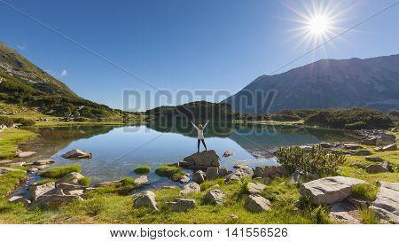 Single woman hiker with white shirt greeting the sun raising his arms in the air near Muratovo lake on the mountain range of National Park Pirin Bulgaria.