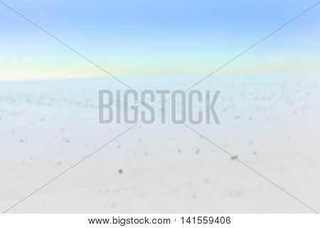 farm field photographed in winter, covered with white snow, blue sky in the background defocus