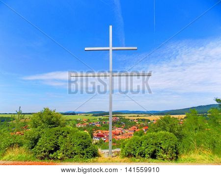 Cross in front of village during sunny day