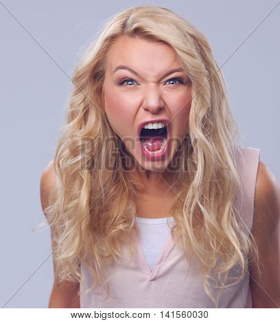 angry woman screaming. Isolated on gray background
