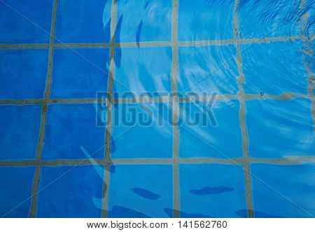 blue tiles in swiming pool wit water wave background