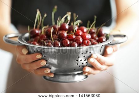 Woman holding colander with cherries