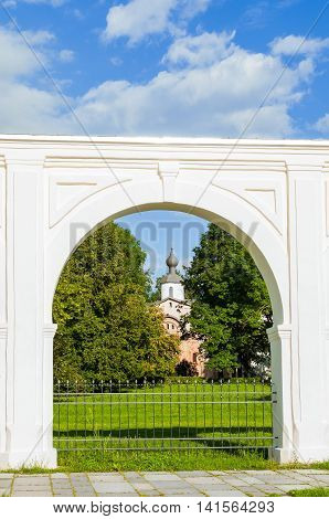 Architecture landscape. Arcade of the ancient Yaroslav courtyard at summer sunny day in Veliky Novgorod Russia - unusual composition with the Paraskeva Pyatnitsa church in one of the arches