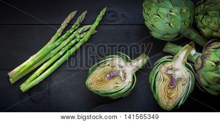 Fresh Green Artichokes And Asparagus On Wooden Table