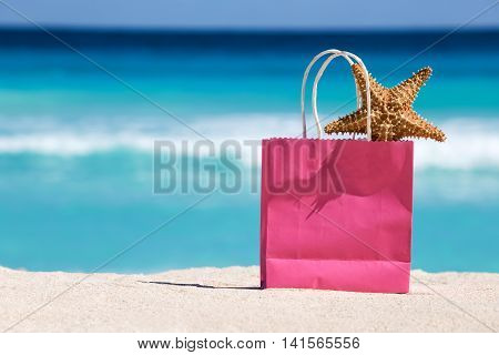 Shopping Bag And Starfish On Sand Against Turquoise Caribbean Sea Water