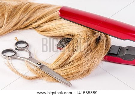 Hairstyling. Closeup blonde woman long haired making hairstyle hairdo with electric hair iron