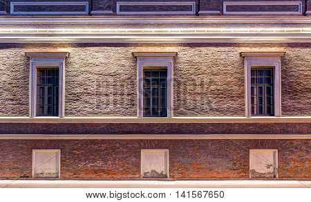 Several windows in a row on night illuminated facade of Central Naval Museum front view St. Petersburg Russia