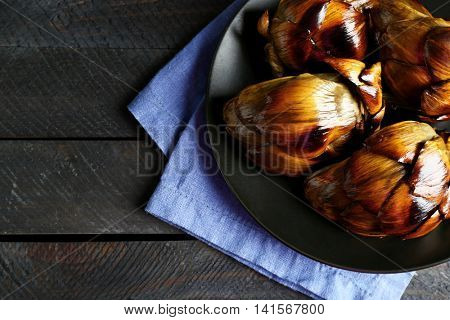 Baked artichokes in black plate, close up