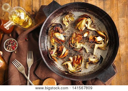 Baked artichokes with spices in a pan on wooden background