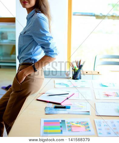 Young woman standing near desk with instruments, plan and laptop