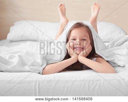 Cute funny girl in white bed