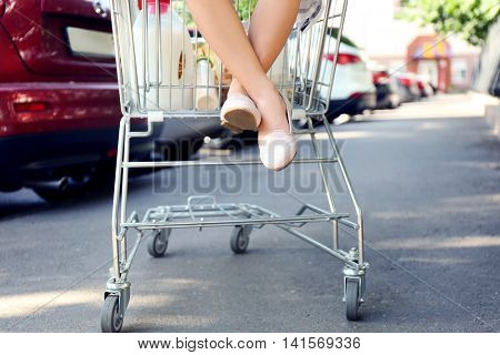 Girl sitting in shopping cart with pack of products, outdoors. Close up of girl's legs