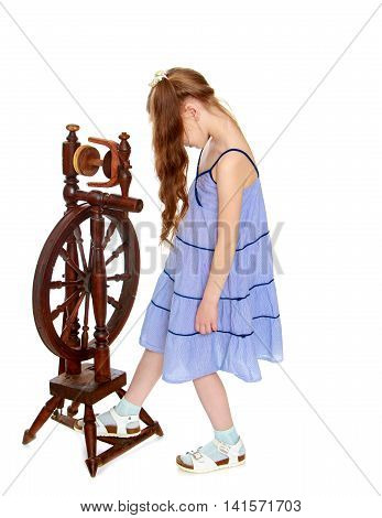 Curious little girl with long pigtails to her waist and braided white bows. In a long blue dress. The girl presses the foot pedal vintage spinning wheels - Isolated on white background
