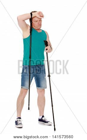 Man in t-shirt and shorts, Nordic walking sticks, hand wipes his sweat from his forehead -Isolated on white background