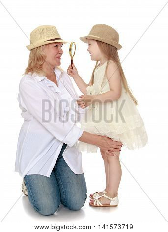 Cute little girl with long blond hair in white dress and hat . The girl looks at through a magnifying glass the face of his beloved grandmother - Isolated on white background