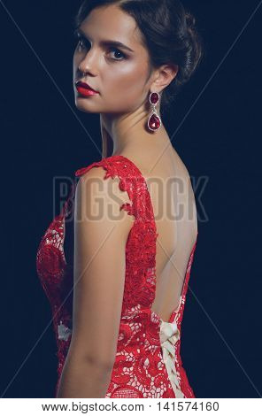 Young beauty woman in red dress. Isolated on black background.