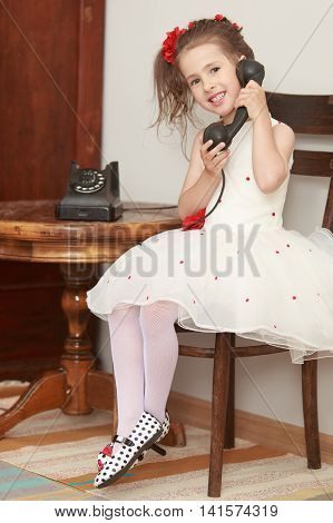 Shy little girl sitting on an old Viennese chair beside a round oak table. Girl holding the ear up the old phone