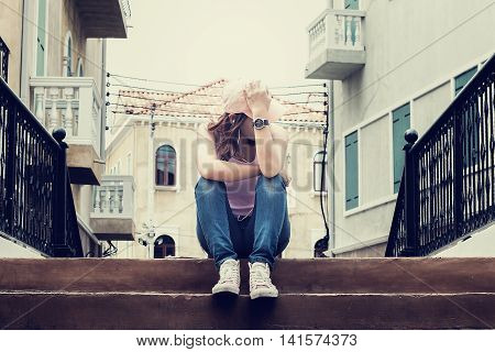 sad woman wearing a hat and hugging knees on stair she is lonely most of the timedark tone