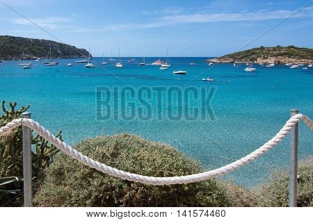 Turquoise Ocean Bay With Boats And Rope Fence