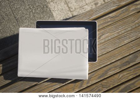 MockUp of the newspaper and tablet on a bench. Moct realistic cover for your design.