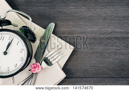 Alarm clock and silverware with a flower on rustic wooden background. Vintage color filtered.