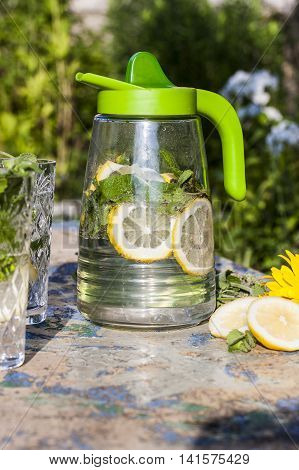 Lemonade pitcher with lemon mint and ice on garden table