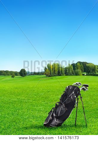 Idyllic golf course with forest and golf bag in the foreground.