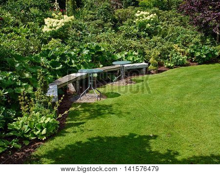Beautiful creative wooden bench in a lush green blooming garden