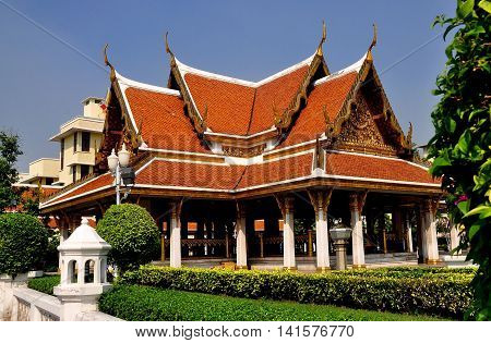 Bangkok Thailand - December 17 2012: An open Sala with orange tiled roofs and gilded chofah ornaments in the gardens at Wat Ratchanadda