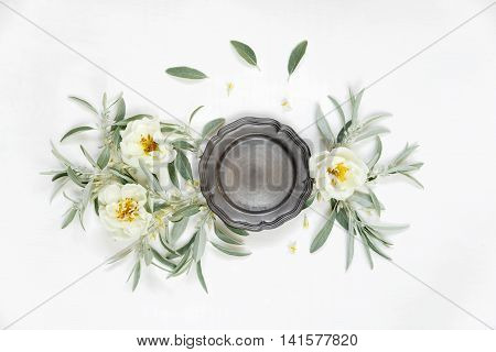 Decorative composition in retro style consisting of vintage metal tray ore retro plate and white rose flowers with green leaves on white background. Top view flat lay