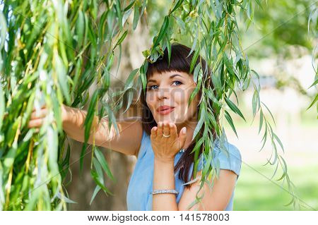 Young beautiful woman sends a kiss and fooling around in the willow branches