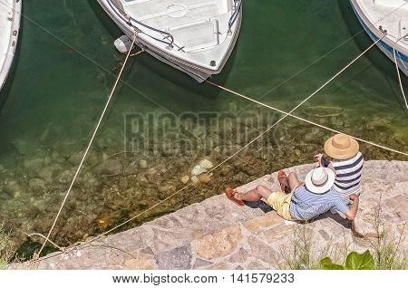 A senior couple relax by the lagoon at Agios Nokolaos on crete.
