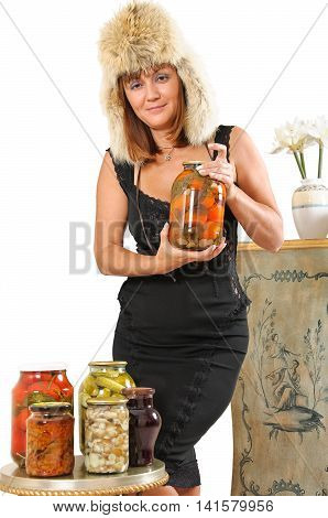 A middle-aged woman in a fur hat and black dress holding a jar with homemade pickles