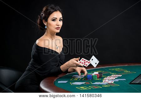 sexy woman with poker cards. Female player in a beautiful black dress. girl sitting at the poker table and throws a cards