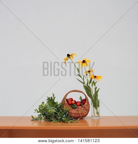 Wicker basket full of red ripe plums branch of unripe fruits and glass vase of beautiful yellow flowers with green leaves on brown wooden school desk on white background