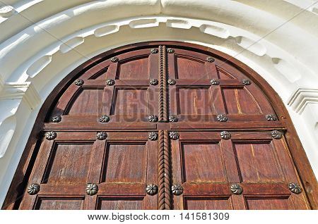 Architecture detailed background - aged wooden door of natural color with metal rivets and upper arch of white stone - vintage architecture background