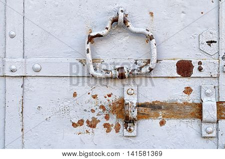 Steel aged painted door with rusty architectural elements - rivets door handle and empty clasp. Retro metal background.